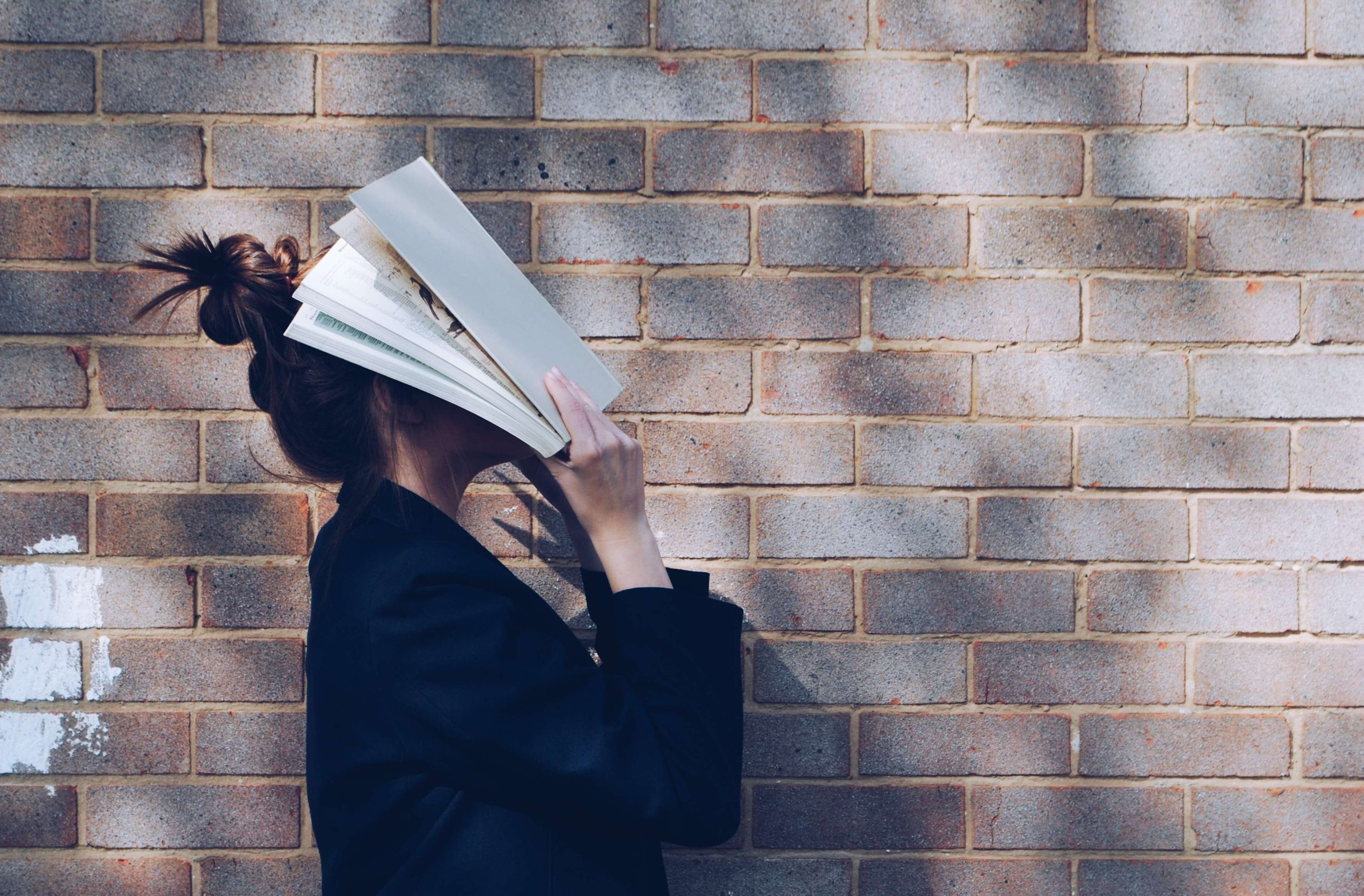 Woman standing next to a brick wall with her head immersed in a book