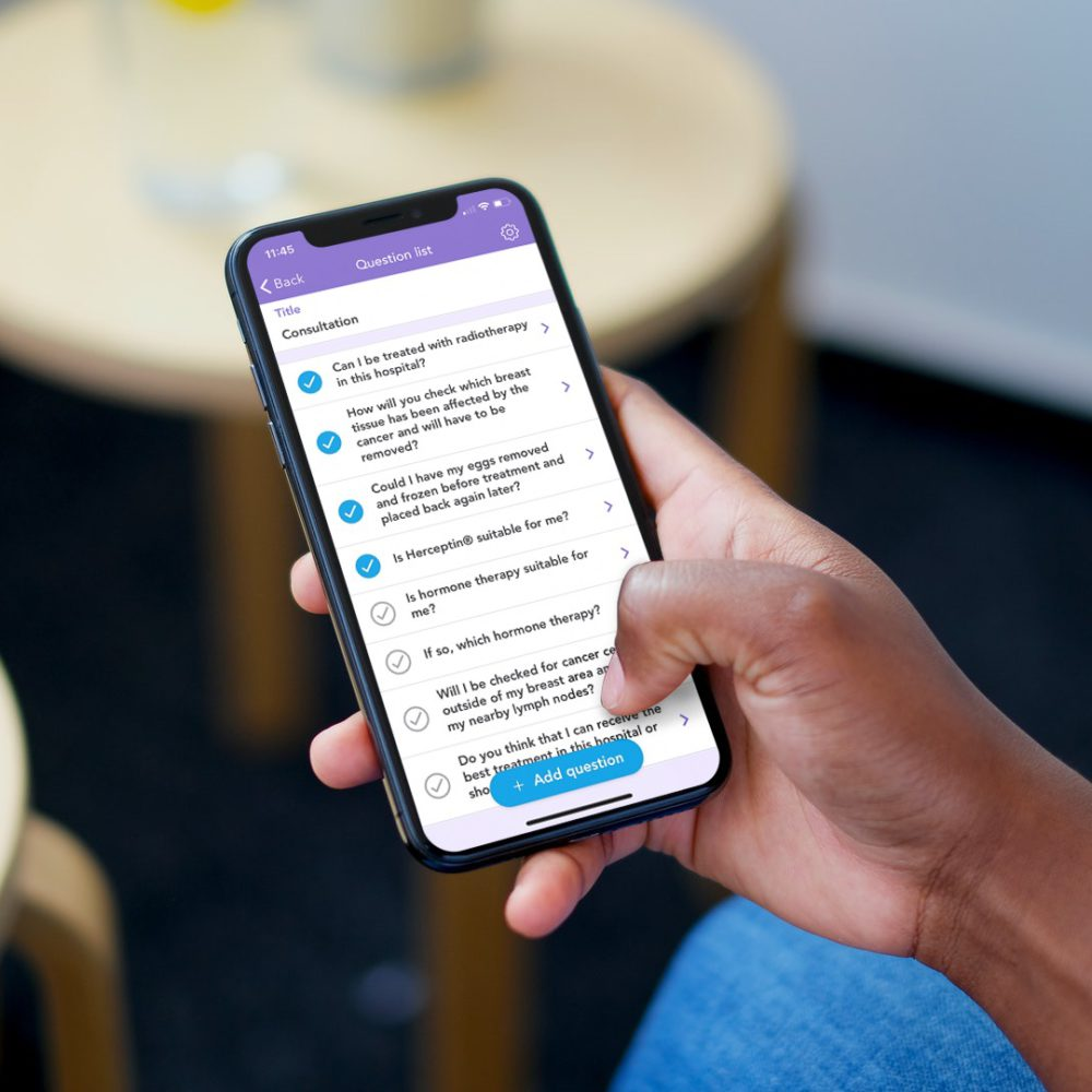 Person sitting at a coffee table holding an iPhone with an OWise question list screenshot